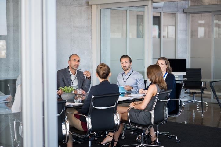 Italienischkurs in einer Firma. Der Lehrer und die Teilenehmenden sitzen um einen Tisch herum.