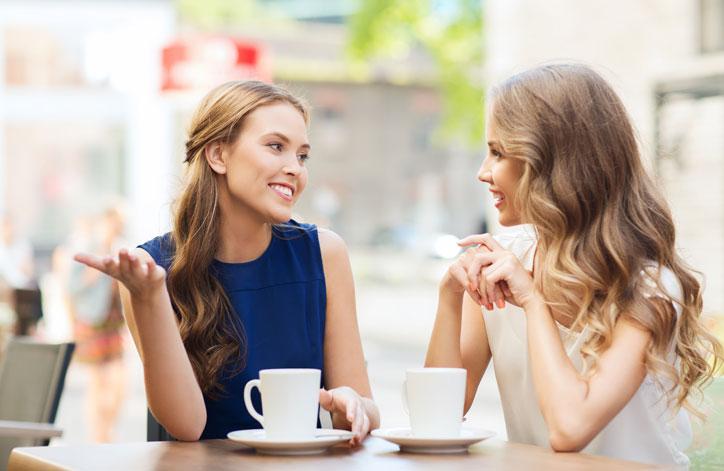 Schwedischkurs im Immersionsunterricht. Lehrerin und Teilnehmerin sitzen in einem Strassencafé und machen Konversation auf Schwedisch.