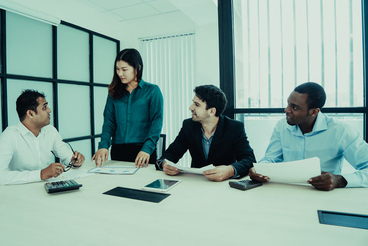 Chinesisch lernen in einer Firma. Die Lehrerin steht bei den Teilnenehmenden, die am Tisch sitzen.