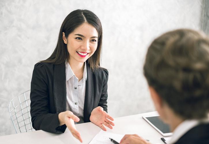 Ein Mann lernt Chinesisch im Einzeunterricht. Die Lehrerin erklärt und hebt dazu ihre Hand.