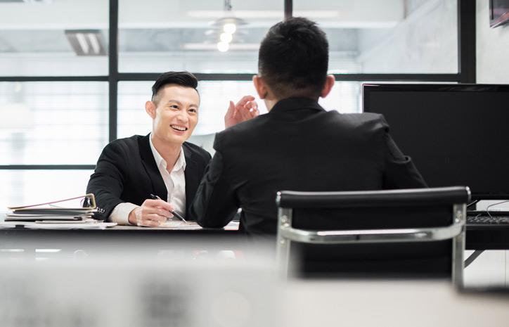 Ein Mitarbeiter lernt Chinesisch im massgeschneiderten Einzelunterricht in der Firma und sitzt mit seinem Chinsischlehrer an einem Tisch.