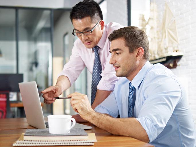 Chinesischkurs im Immersionsunterricht. Der Lehrer steht neben dem am Tisch sitzenden Teilnehmer und erklärt etwas auf den Laptop.