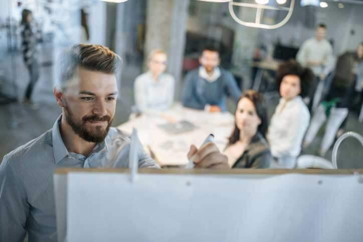 Deutschkurs in einer Firma. Der Lehrer schreibt an ein Flipchart, die Kursteilnehmer sitzen um einen Tisch.