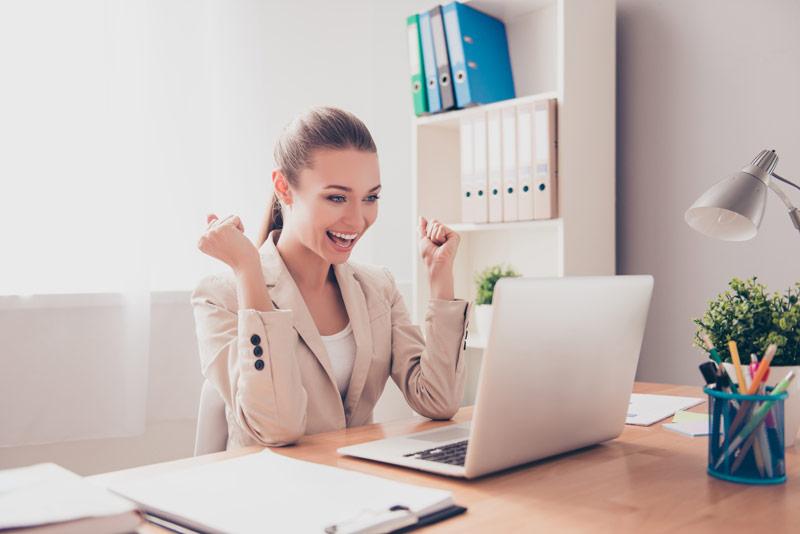 Eine Businessfrau sitzt im Büro und jubelt, weil sie ihr Sprachdiplom bestanden hat.