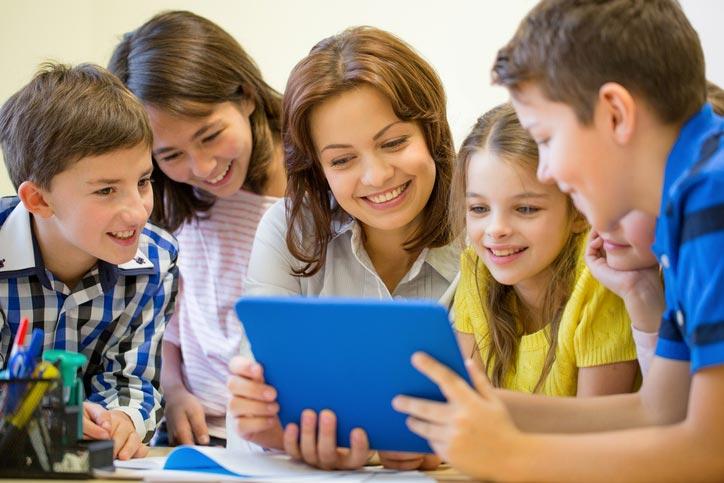 Eine kleine Gruppe Kinder lernt Englisch und schaut sich etwas auf einem Tablett an. Die Gruppe steht um die Englisch-Lehrerin herum.