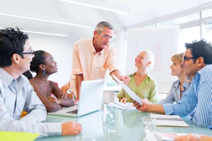 Französischkurs in einer Firma. Der Lehrer spricht zu den multikultirellen Mitarbeitern, die um einen Tisch herum sitzen.