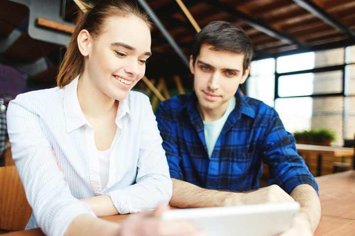 Französischkurs im intensiven Einzelunterricht. Die Lehrerin und der Schüler sitzen am Tisch.