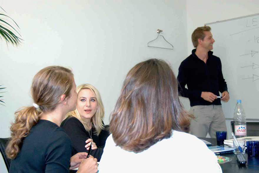 Französischkurs in einer kleinen Gruppe in der Sprachschule Schneider. Der Französischlehrer schreibt an die Tafel.