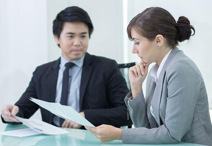Eine Frau lernt Japanisch im Einzeunterricht. Der Lehrer sitzt neben ihr am Tisch.