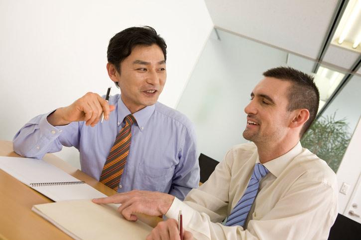 Ein Mitarbeiter lernt Japanisch im massgeschneiderten Privatunterricht in der Firma und sitzt neben dem Lehrer am Tisch.