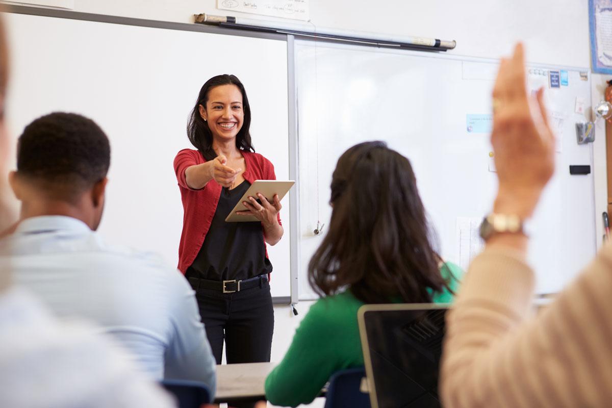 Spanischkurs in Zürich in einer kleinen Gruppe. Die Lehrerin erklärt am Flipchart, den Spanisch lernenden zugewandt und lacht diese an.
