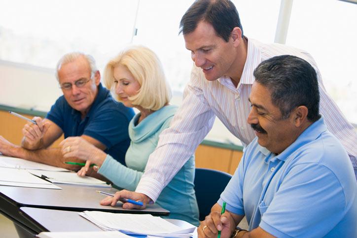 Portugiesisch lernen in einer Firma. Der Lehrer steht bei den Teilenehmenden, die am Tisch sitzen und schaut sich die Hausaufgaben der Schüler an.