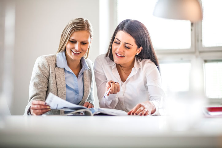 Eine Geschäftsfrau lernt Portugiesisch im massgeschneiderten Einzelunterricht. Ihre Lehrerin sitzt nahe bei ihr und zeigt auf einen Text.