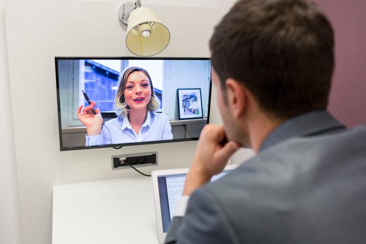 Eine junger Mann lernt Russisch online via Videokonferenz. Die Lehrerin erklärt und hebt dazu ihre Hand.