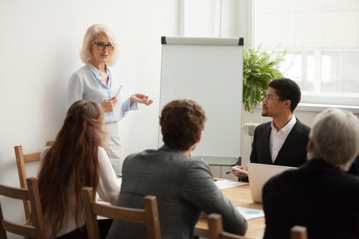 Schwedisch lernen in einer Firma. Die Lehrerin steht beim Flipchart und spricht zu den Teilnenehmenden, die am Tisch sitzen.