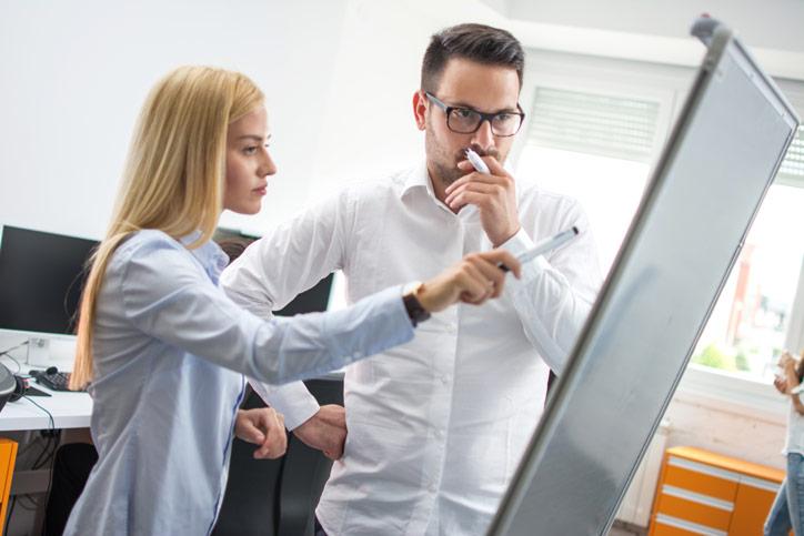 Ein Mitarbeiter lernt Schwedisch im massgeschneiderten Privatunterricht in der Firma und mit der Lehrerin beim Flipchart.