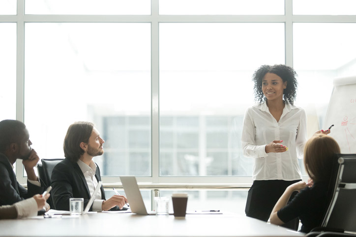 Spanisch lernen in einer Firma. Die Lehrerin steht beim Flipchart, die Teilnehmenden sitzen um einen Tisch herum.