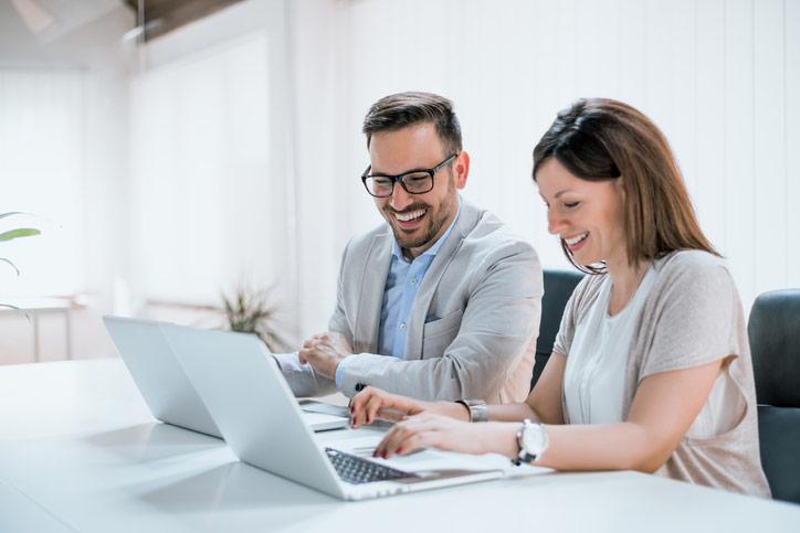 Ein Businessmann lernt Spanisch im massgeschneiderten Einzelunterricht. Seine Lehrerin und er haben einen Laptop vor sich.