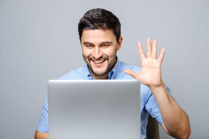 Eine junger Mann lernt Spanisch online via Videokonferenz und winkt seiner Lehrperson zu. - Fotograf > getty images