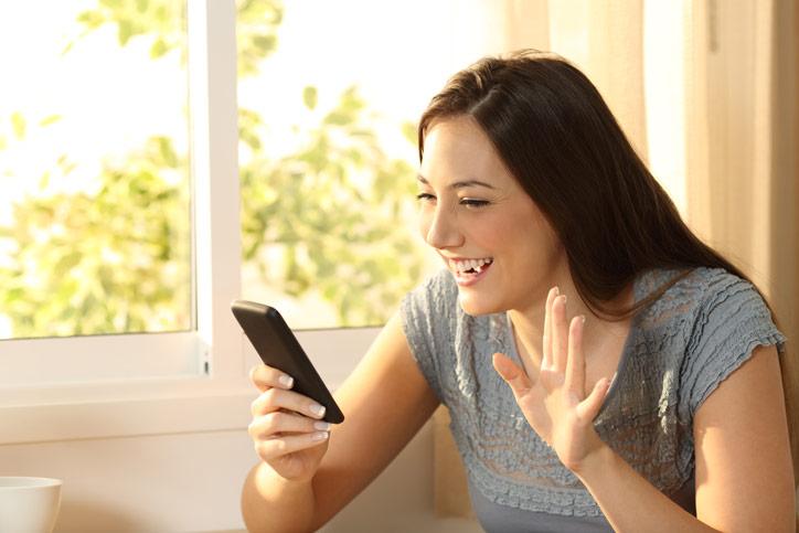 Eine junge Frau begrüsst ihre online Nachhilfelehrperson auf dem Handy